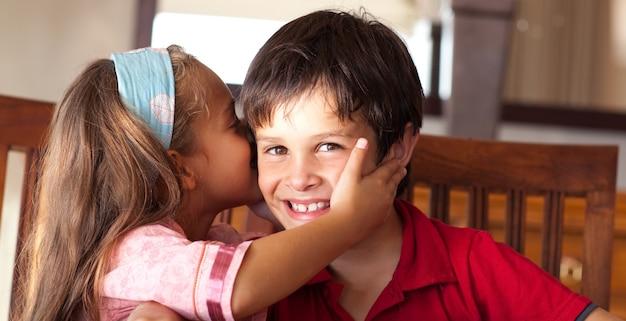 Menina linda que beija seu irmão