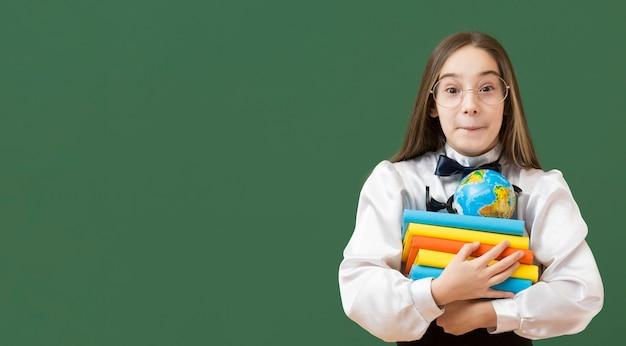 Menina linda segurando o espaço de cópia de pilha de livro