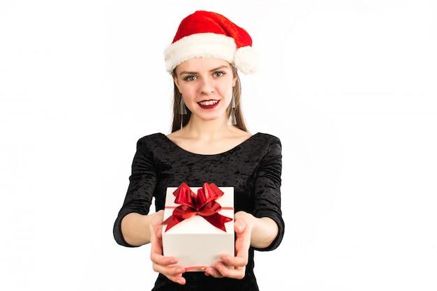 Menina linda segurando o presente e sorrindo para a câmera em branco isolado