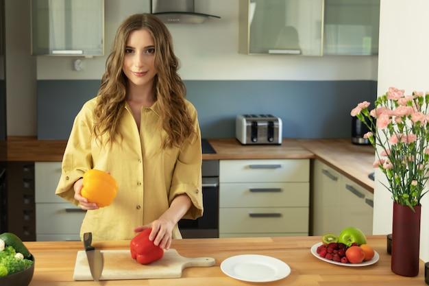 Menina linda segurando um pimentão nas mãos dela. uma mulher prepara uma salada de legumes frescos e saudáveis.