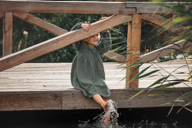 Menina linda sozinha em um píer de madeira na margem do lago