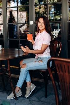 Menina lindamente vestida, sentado no café a beber café.