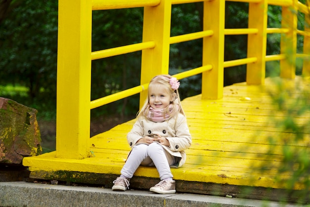 Menina llittle elegante em uma ponte amarela no parque