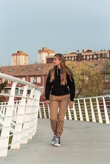 Menina loira adolescente andando em uma ponte urbana branca. edifícios residenciais ao fundo.