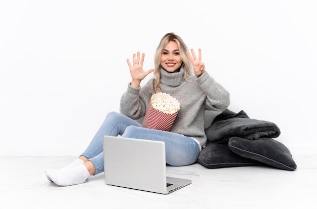 Menina loira adolescente comendo pipoca enquanto assiste a um filme no laptop contando oito com os dedos
