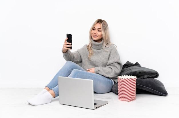 Menina loira adolescente comendo pipoca enquanto assiste a um filme no laptop fazendo uma selfie