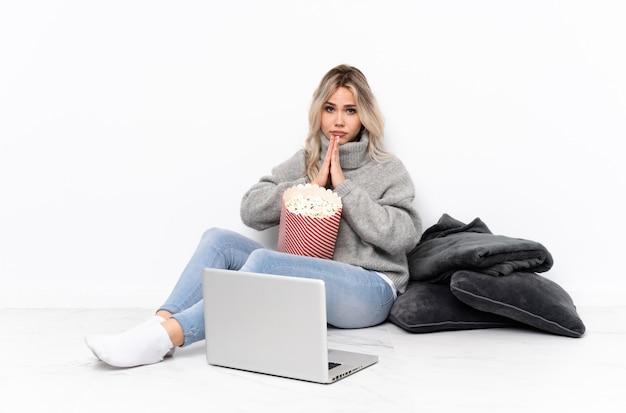 Menina loira adolescente comendo pipoca enquanto assiste a um filme no laptop mantém a palma da mão