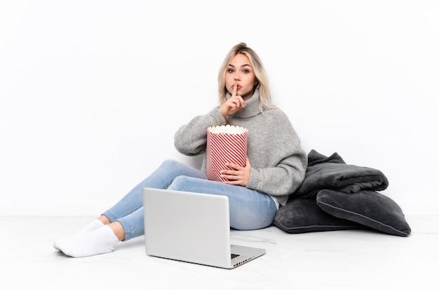 Menina loira adolescente comendo pipoca enquanto assiste a um filme no laptop mostrando um sinal de gesto de silêncio colocando o dedo na boca