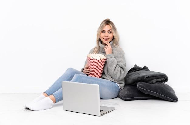 Menina loira adolescente comendo pipoca enquanto assiste a um filme no laptop olhando para o lado