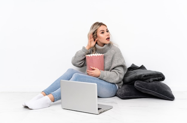 Menina loira adolescente comendo pipoca enquanto assiste a um filme no laptop ouvindo algo colocando a mão na orelha