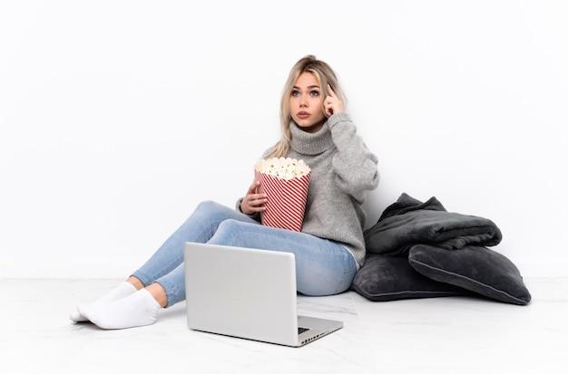 Menina loira adolescente comendo pipoca enquanto assiste a um filme no laptop tendo dúvidas e pensando