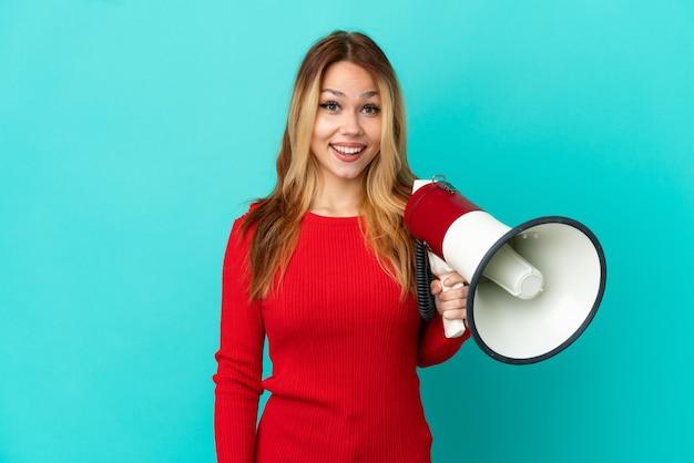 Menina loira adolescente em um fundo azul isolado segurando um megafone e com expressão de surpresa