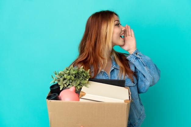 Menina loira adolescente fazendo um movimento enquanto pegava uma caixa cheia de coisas gritando com a boca aberta para o lado