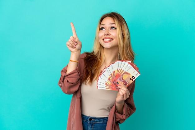 Menina loira adolescente pegando muitos euros sobre um fundo azul isolado apontando com o dedo indicador uma ótima ideia