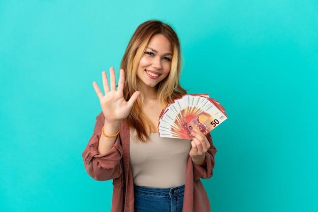 Menina loira adolescente pegando muitos euros sobre um fundo azul isolado, contando cinco com os dedos