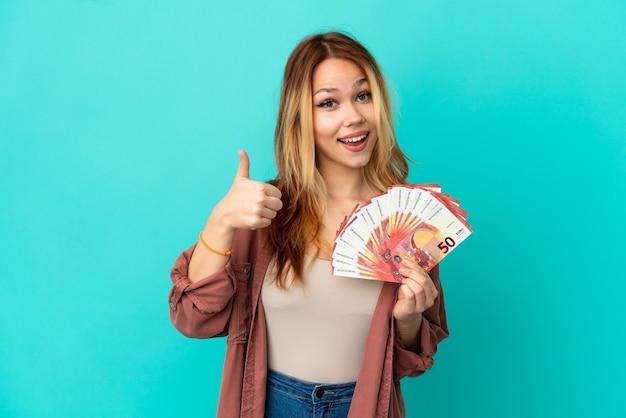 Menina loira adolescente pegando muitos euros sobre um fundo azul isolado, mostrando o sinal de ok e o gesto do polegar para cima