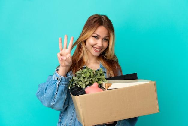 Menina loira adolescente se mexendo enquanto pega uma caixa cheia de coisas felizes e conta três com os dedos