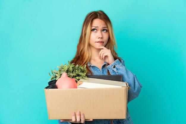 Menina loira adolescente se mexendo enquanto pega uma caixa cheia de coisas, tendo dúvidas e pensando