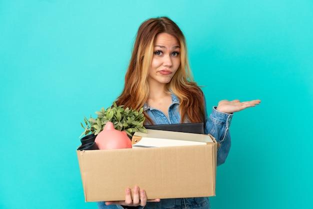 Menina loira adolescente se mexendo enquanto pega uma caixa cheia de coisas, tendo dúvidas enquanto levanta as mãos