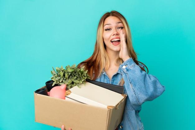 Menina loira adolescente se mexendo enquanto pegava uma caixa cheia de coisas gritando com a boca bem aberta