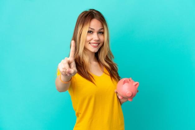 Menina loira adolescente segurando um cofrinho sobre um fundo azul isolado, mostrando e levantando um dedo