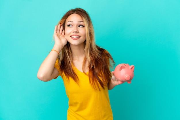 Menina loira adolescente segurando um cofrinho sobre um fundo azul isolado, ouvindo algo colocando a mão na orelha
