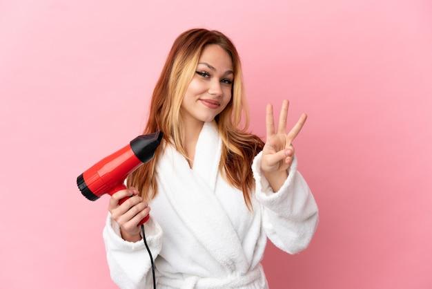 Menina loira adolescente segurando um secador de cabelo sobre um fundo rosa isolado feliz e contando três com os dedos