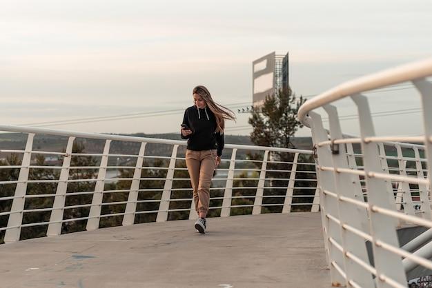 Menina loira adolescente usando seu telefone celular. andando em uma ponte urbana branca.