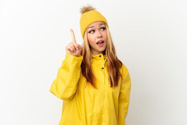 Menina loira adolescente vestindo um casaco à prova de chuva sobre um fundo branco isolado com a intenção de perceber a solução enquanto levanta um dedo