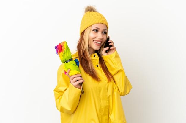 Menina loira adolescente vestindo um casaco à prova de chuva sobre um fundo branco isolado, conversando com o telefone celular