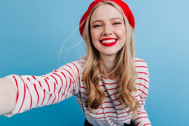Menina loira animada na boina tomando selfie na parede azul. jovem despreocupada com camisa listrada.