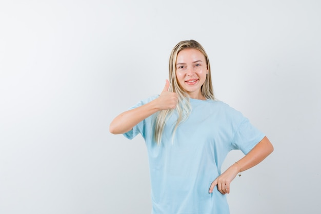 Menina loira aparecendo o polegar, segurando a mão na cintura em uma camiseta azul e parecendo confiante, vista frontal.