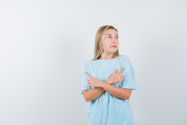 Menina loira apontando direções opostas, mordendo os lábios em uma camiseta azul e está linda. vista frontal.