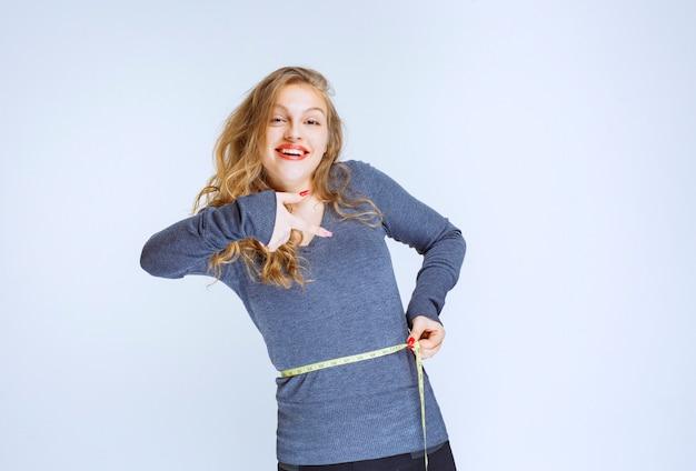 Menina loira apontando para o tamanho da cintura dela.