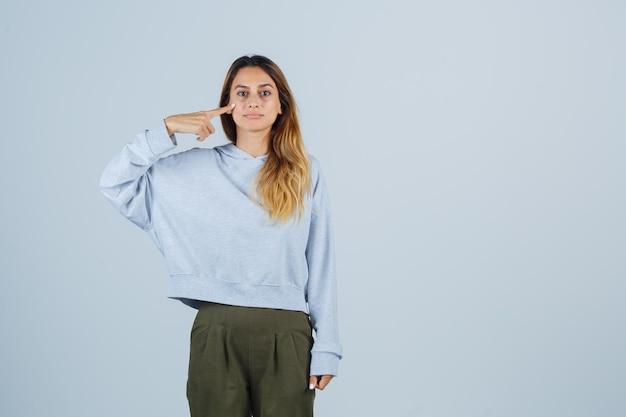 Menina loira apontando para si mesma com o dedo indicador em moletom azul verde oliva e calças e olhando séria. vista frontal.