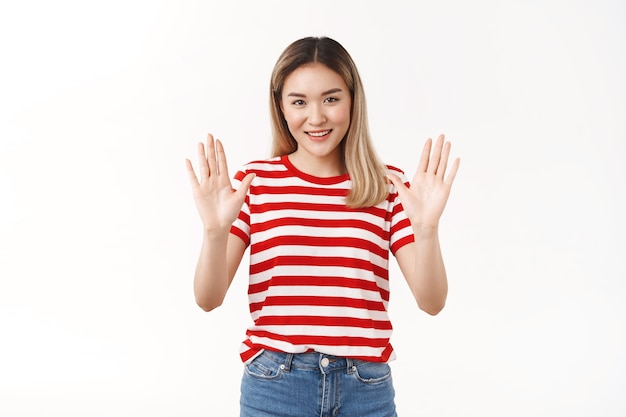 Menina loira asiática otimista assertiva garantindo tudo bem perguntando relaxe, relaxe, levante as mãos, segure calma, sorrindo amigável, diga ao amigo que não se preocupe