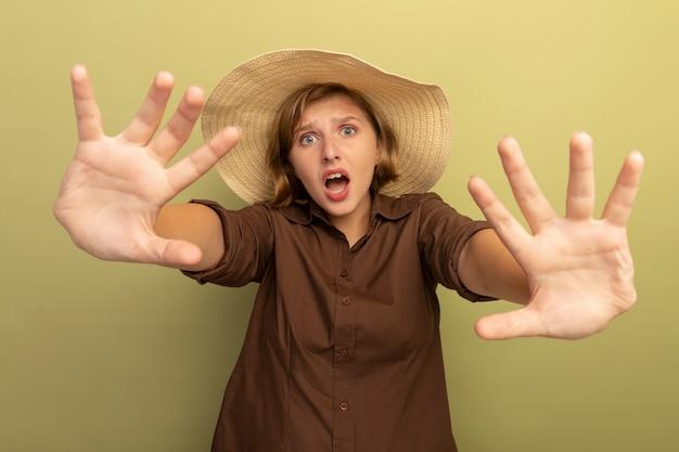 Menina loira assustada com chapéu de praia fazendo gesto de parada isolado na parede verde oliva