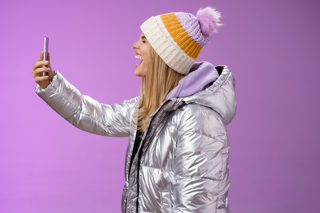 Menina loira atraente divertida e despreocupada com uma jaqueta de inverno prateada chapéu estender o braço segurando um smartphone