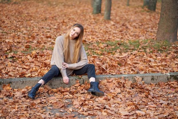 Menina loira atraente hippie vestindo um suéter superdimensionado elegante, jeans preto da moda da mãe e botas de couro preto jovem sentado no parque outono.