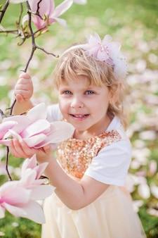 Menina loira bonita 3 anos joga em um parque perto de uma magnólia em flor. primavera.
