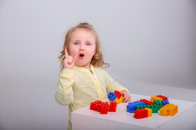 Menina loira bonita brincando em um construtor. conceito de educação pré-escolar