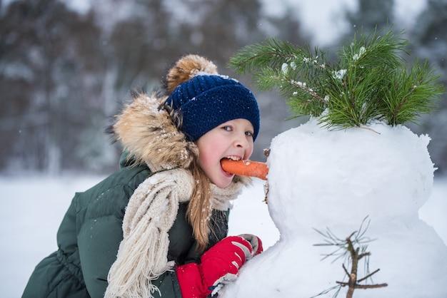 Menina loira bonita criança feliz comendo boneco de neve nariz de cenoura