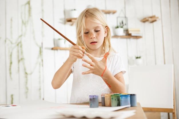 Menina loira bonita e bonita em camiseta branca, alegremente, pintando a palma da mão com pincel, em pé atrás da mesa com jarra de água, pincéis e tinta sobre ele.