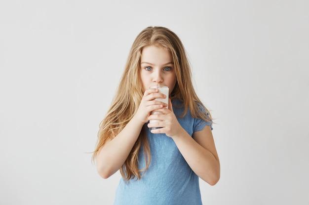 Menina loira bonitinha com encantadores olhos azuis concentrada olhando e copo de leite. momentos felizes da infância.