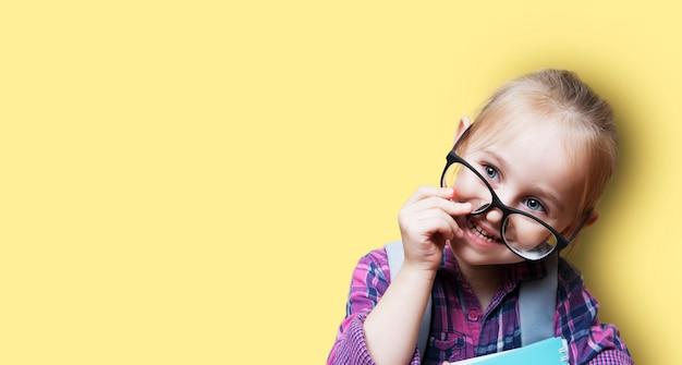 Menina loira bonitinha de óculos com uma mochila em um fundo laranja. ensinar o conceito de pré-escolares. banner com espaço de cópia