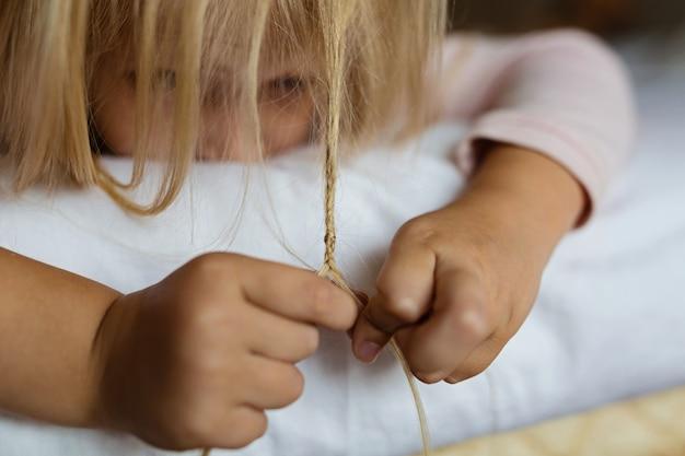 Menina loira bonitinha de pijama brincando na cama branca, de manhã cedo antes de ir para o jardim de infância