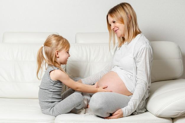 Menina loira brincando com a barriga da mãe grávida