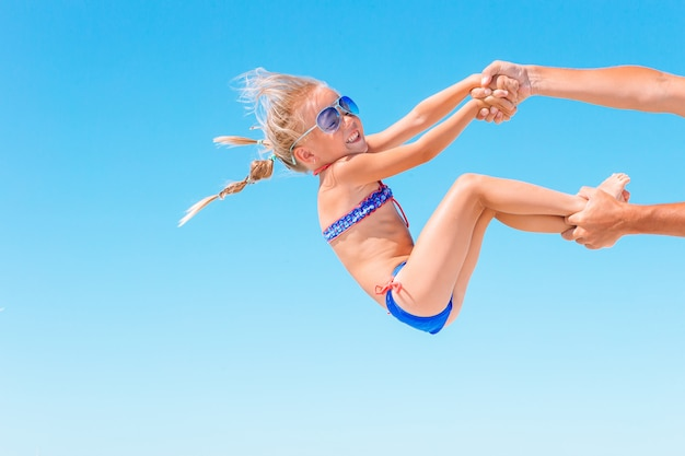 Menina loira brincando com seu pai na praia