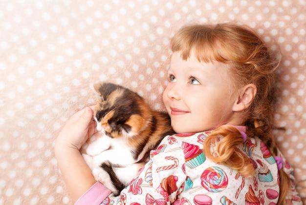 Menina loira brincando com um gatinho malhado