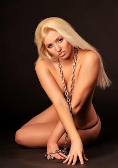 Menina loira caucasiana branca acorrentada em roupa interior sentado e posando. mulher segurando as mãos perto do pescoço no retrato de correntes. isolado em parede escura